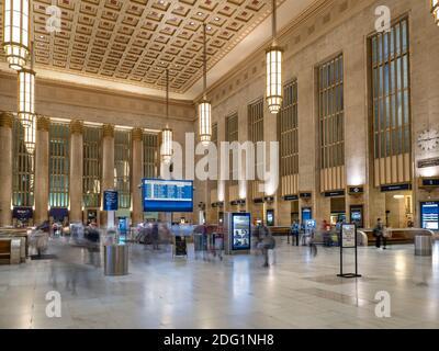 Interior of 30th Street Railway Station with blurry passenger travelers, Philadelphia, USA