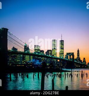 New York 1985, Brooklyn bridge, East river, Manhattan skyline, WTC World Trade Center twin towers in the distance, dusk, New York City, NY, NYC, USA,