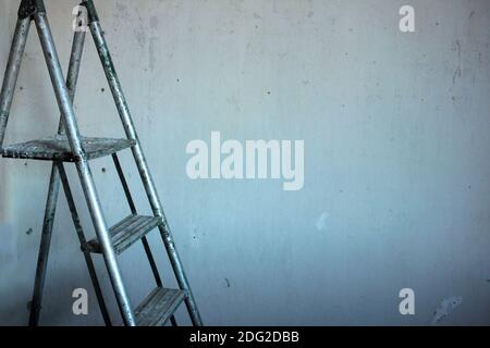 Old metal ladder near a shabby wall during repair work. Textured concrete wall background with copy space. - Stock Photo