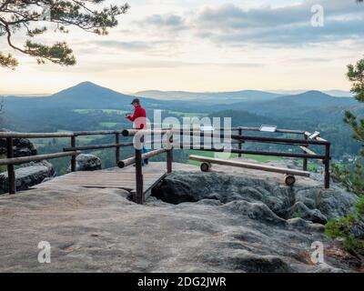 Man on rock shoots mountain landscape photos. Traveler with camera takes breathtaking panorama of mountains viewpoint - Stock Photo