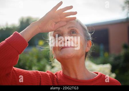 Portrait of senior woman with grey hair and face with wrinkles wearing red knitted sweater and relaxing at park during sunny day and looking for