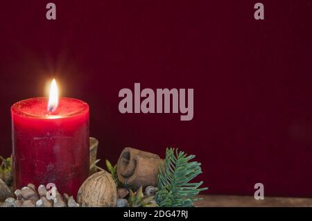 Background Christmas decoration, red candle with candlelight in front of red velvet and copy space.