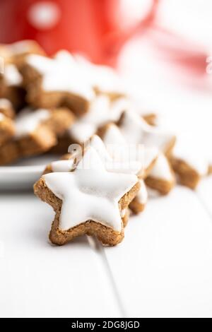 Icing gingerbread stars. Traditional Christmas cookies on white table.