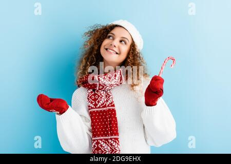 cheerful woman in red mittens holding candy cane on blue