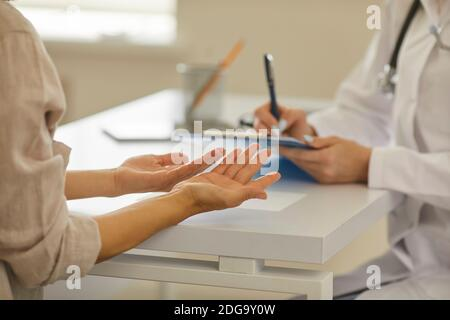Close up of hands of doctor and patient discussing diagnosis sitting in hospital office Stock Photo