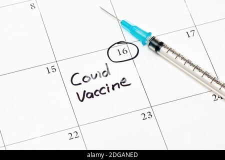 Covid-19 coronavirus vaccine reminder on calendar with syringe and needle. Concept of vaccination, herd immunity and pandemic healthcare. - Stock Photo