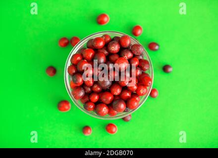 Fresh red cranberries in a glass bowl on green background - Stock Photo