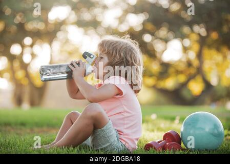 Funny child sport. Drinking water concept. Kid boy with bottle of water. Kid with drink water in park. Children development and healthy strong