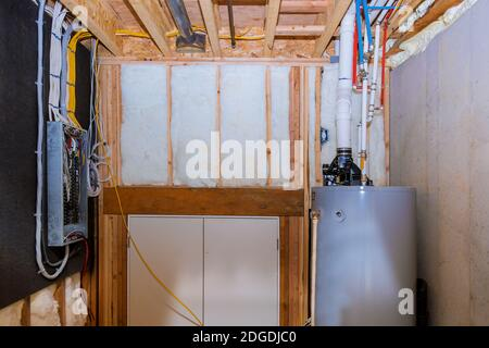 Boiler and pipes of the heating system a home framing with basement, control panel with wiring terminals in the electrical