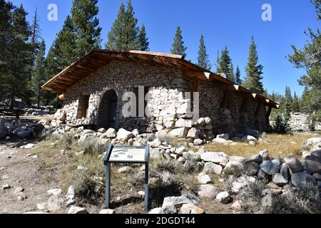 Parsons Lodge, A stone and wooden hut structure in Tuolumne Meadows, Yosemite National Park, USA. A sign with information for visitors stands outside.