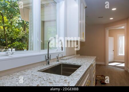 New modern white kitchen with built chrome water tap