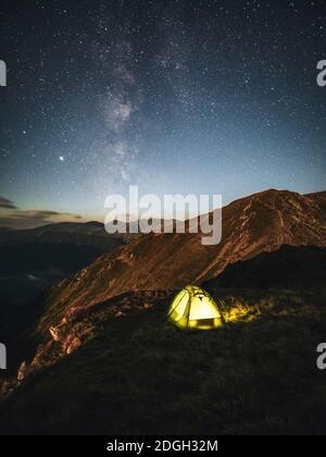 Camping under starry sky and milky way at high altitude on the Carpathian mountains. Illuminated tent in the foreground and majestic mountain peak