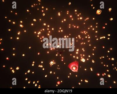 A beautiful views of sky lanterns being released into the dark sky - Stock Photo