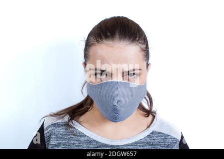 Caucasian young woman in medical mask with angry look on a white background.