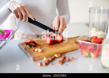 close up young beautiful girl is cutting fresh strawberries on kitchen counter preparing them to be blended with bananas for a smoothie.