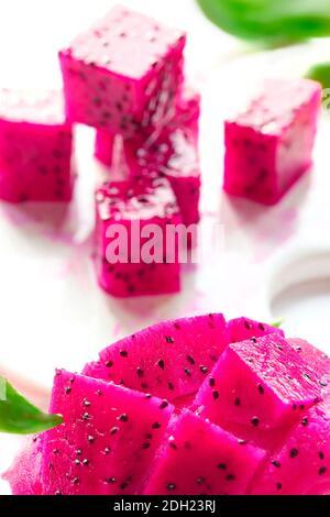 Pink dragon fruit, pitaya or pitahaya cut in cubes on cutting board. Trendy superfood.