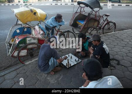 Drivers play chess sitting on the pavement next to their cycle rickshaws known locally as the becaks in Alun Alun Utara square in Yogyakarta in Central Java, Indonesia.