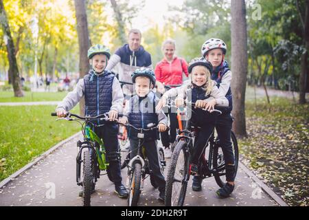 Theme family sports vacation in park in nature. big friendly Caucasian family of six people mountain bike riding in forest. Chil