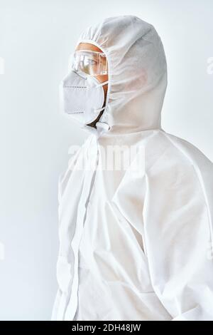 Profile view of doctor in protective medical suit, face mask and glasses - Stock Photo