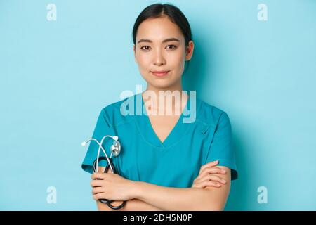 Covid-19, social distancing and coronavirus pandemic concept. Close-up portrait of confident smiling asian female doctor, nurse