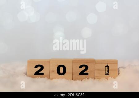 New year 2021 on wooden cubes with vaccine syringe. Concept of Covid-19 vaccination - Stock Photo