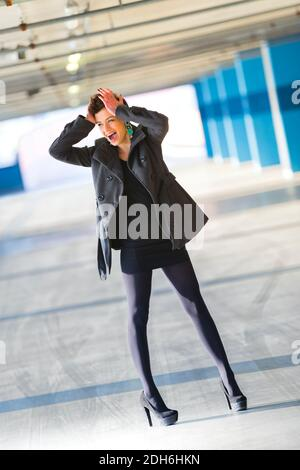 Teengirl legs heels Black outfit is panicking freaking out both hands are holding hold head hair shorthaired shorthair looking away aside legs heels Stock Photo