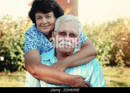 Loving mature cople hugs on a summer day in the park.Senior couple are sitting outdoors.An elderly woman hugs an old man