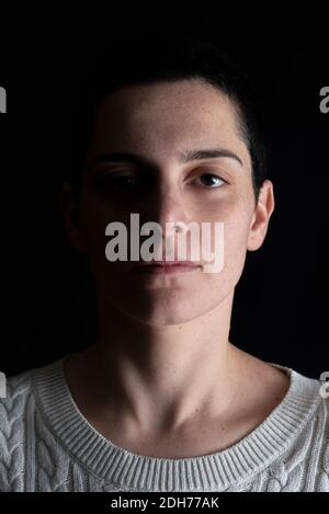 Shadowy portrait of beautiful woman looking at camera