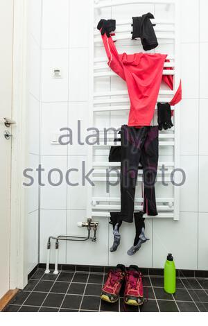 Sports clothing hanging on racks in bathroom - Stock Photo