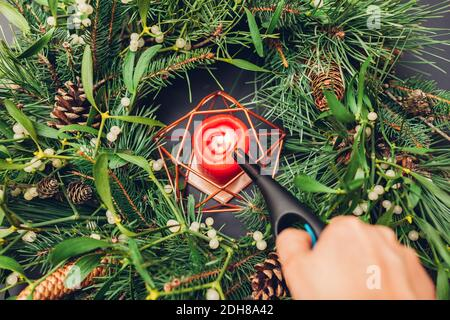Woman lights up candle inside Christmas and New Year wreath made of fir, pine, mistletoe branches, cones. Eco and natural home decoration