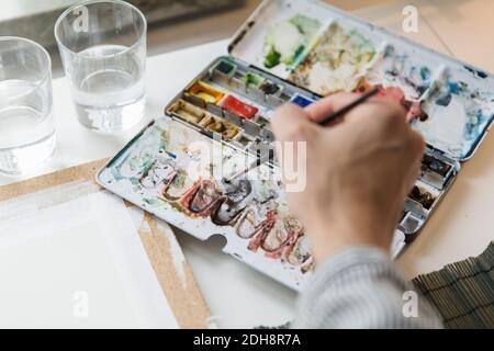 Cropped image of artist mixing watercolor paints while working in creative office
