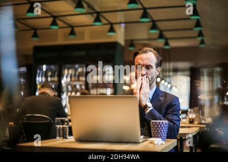 Worried businessman looking at laptop in restaurant
