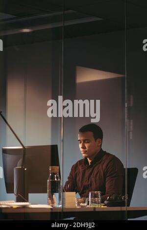 Tired businessman working at desk in dark office