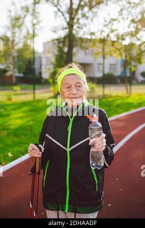 Age maturity, active lifestyle and wellness. Joyful retired woman with walking poles and bottle of water, refreshing during phys