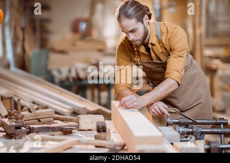Handsome carpenter working with a wood, marking plank with a pencil in the carpentry workshop