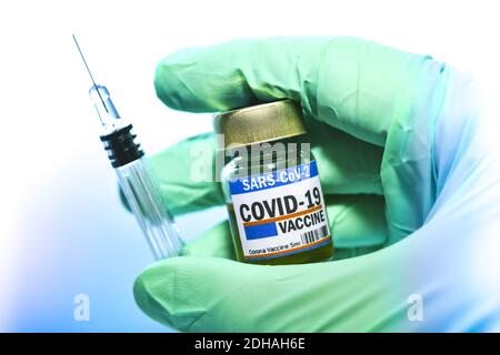 Hand im Latexhandschuh hält Injektionsfläschchen mit Corona-Impfstoff und Impfspritze, Symbolfoto Corona-Impfmittel Stock Photo