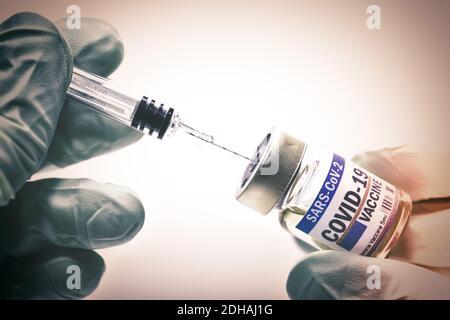 Hände in Schutzhandschuhen halten Injektionsfläschchen mit Corona-Impfstoff und Impfspritze, Symbolfoto Corona-Impfmittel Stock Photo
