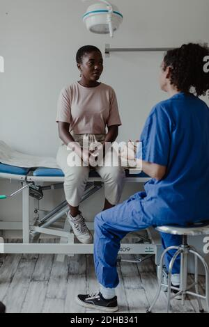 Female doctor discussing with patient in medical room at hospital