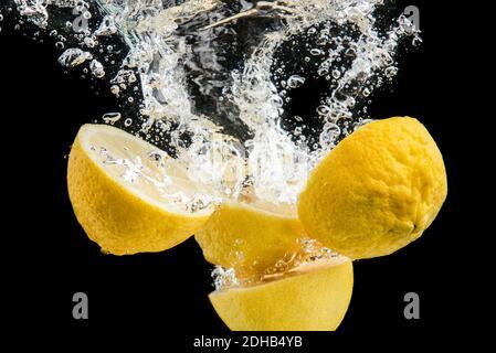 Fresh yellow lemons in water splash on black background
