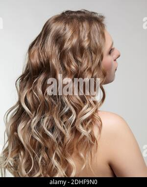 Woman from backside on gray background. Female with curly hair