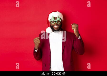 Merry Christmas. Cheerful Black man wearing funny party glasses and santa hat, smiling joyful, celebrating winter holidays, stan