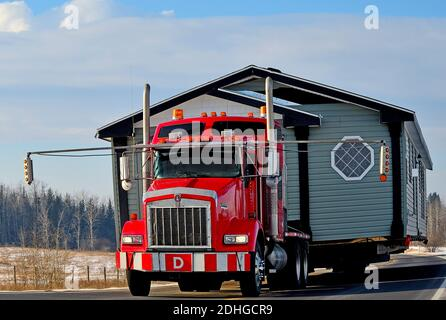 A close up image of a red semi truck moving a house along a two lane highway in rural Alberta Canada - Stock Photo