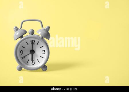 Gray analogue alarm clock showing six in the morning on background of the illuminating yellow tone. Copy space. The main color trend of the year 2021.