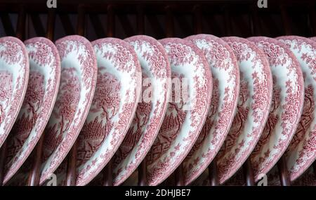 Ceramic plates with patterns on the shelf close-up in row