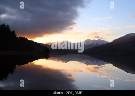 Sunset over the Snowdon horseshoe across showing recent snowfall beyond a flat calm Llynnau Mymbyr. Wales.   Picture taken 5th December 2020