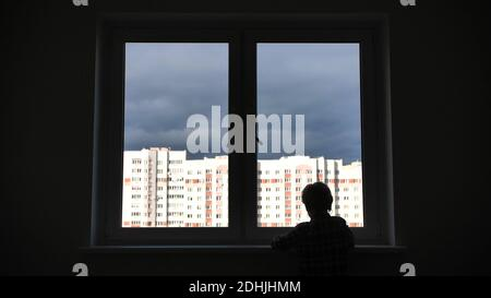 A lonely child looks out the window of his house in an apartment.