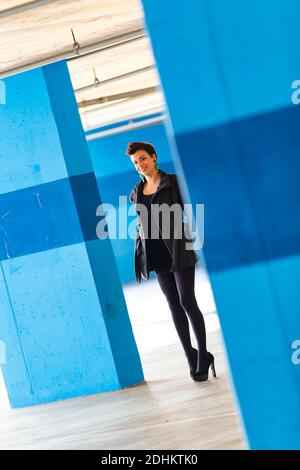 Teengirl in empty parking lot with Blue walls legs heels eyeshot eyes eye contact looking at camera tight space Stock Photo