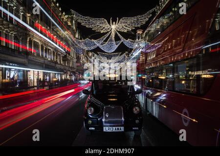 Golden angel christmas decorations and light trails on Regent Street.
