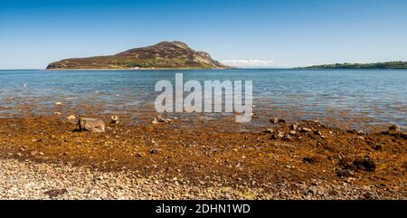 Sun shines on Holy Island in Lamlash Bay off the coast of Arran in Scotland's Firth of Clyde. - Stock Photo