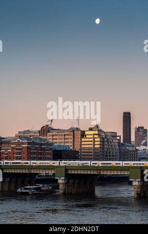 London, England, UK - January 4, 2010: A Thames Clipper and SouthEastern railway train take commuters past office blocks on the River Thames in centra - Stock Photo